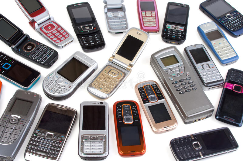 Different cell phones. Many different cell phones, old ones and newer ones, white background