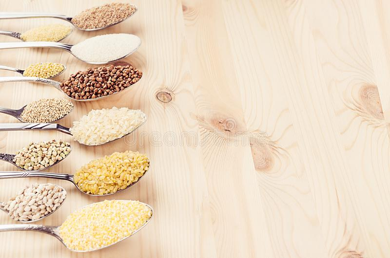 Different cereals grain in spoons with blur on beige wood board, healthy food background. Different cereals grain in spoons with blur on beige wood board stock images