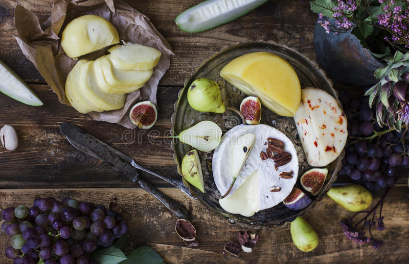 Different cheese, fresh fruits and garden flowers on old wooden background royalty free stock images
