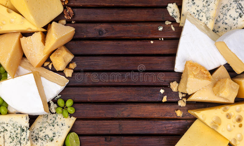 Different cheeses on wooden table with empty space. Cheddar, parmesan, emmental, blu cheese. Top view, copy space. royalty free stock photos