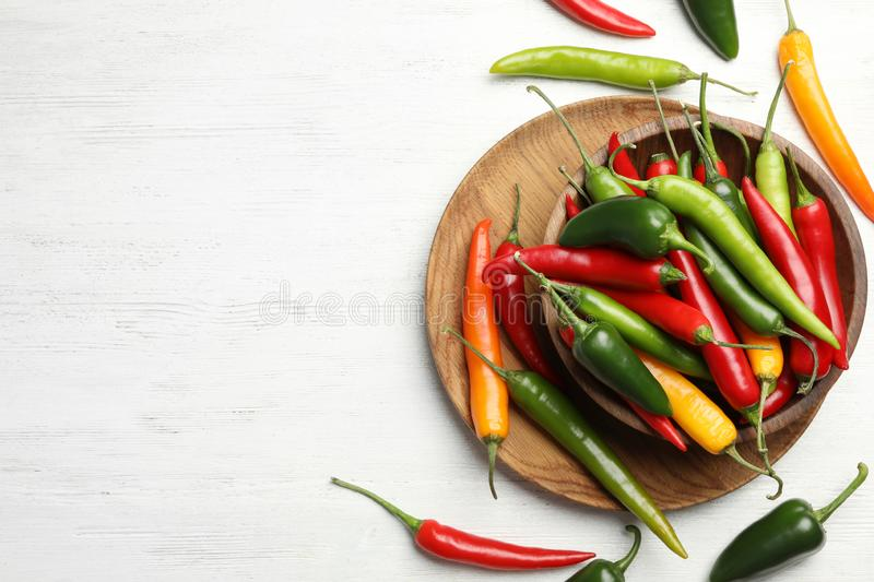 Different chili peppers on white table, flat lay. Space for text. Different chili peppers on white wooden table, flat lay. Space for text royalty free stock image