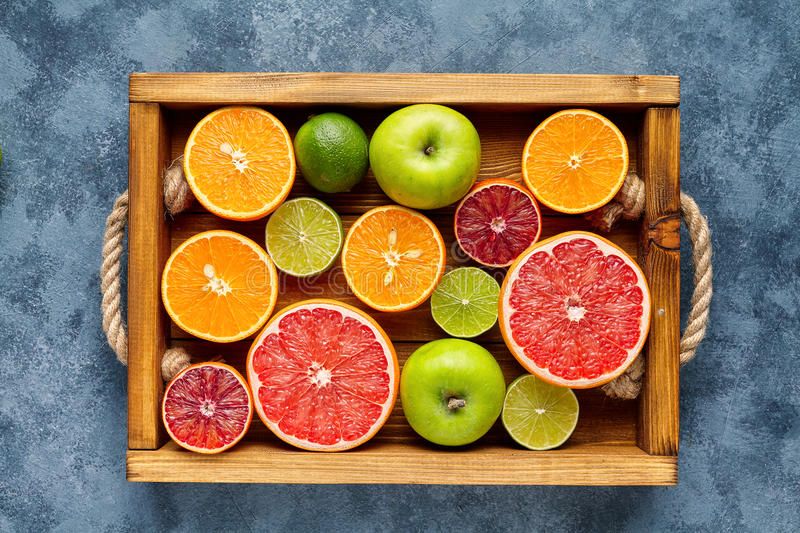 Different citrus fruit on a wooden box and grey concrete table. Food background. Healthy eating. Antioxidant, detox royalty free stock images