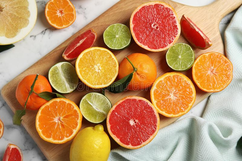 Different citrus fruits on marble background. Top view royalty free stock image