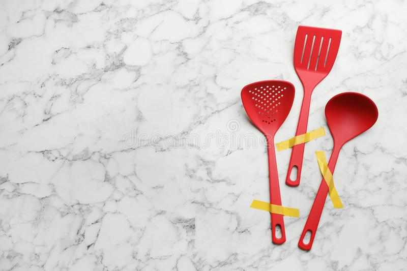 Different clean kitchen utensils on marble background, flat lay. Space for text stock photography
