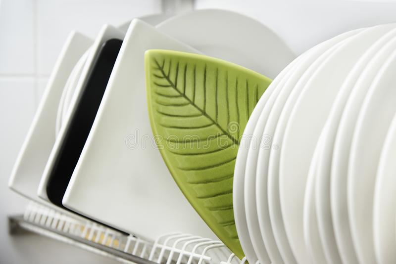 Different clean plates in dish drying rack stock photography