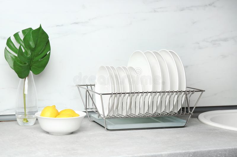 Different clean plates in dish drying rack royalty free stock photos
