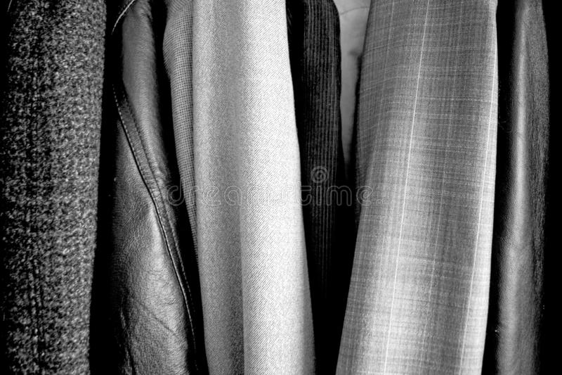 Different clothes placed in the wardrobe. Black and white. Good texture stock image