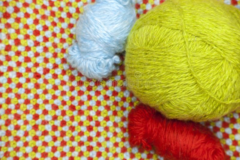 Different coils of red, blue and green yarn on a background of knitted, woolen cloth stock photo
