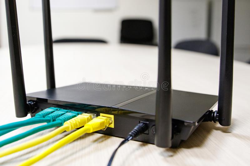 Different color cable connected to the router in different ports in the background wall of the room stock photos