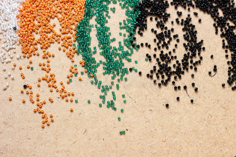 Different color Mardi Gras beads scattered on top of each other, giving a vibrant color splash background. Scattered colored beads. Different color Mardi Gras stock photos