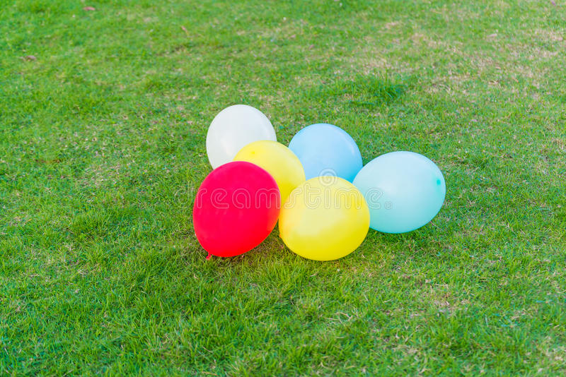 Different colored balloons in the grass. royalty free stock photo
