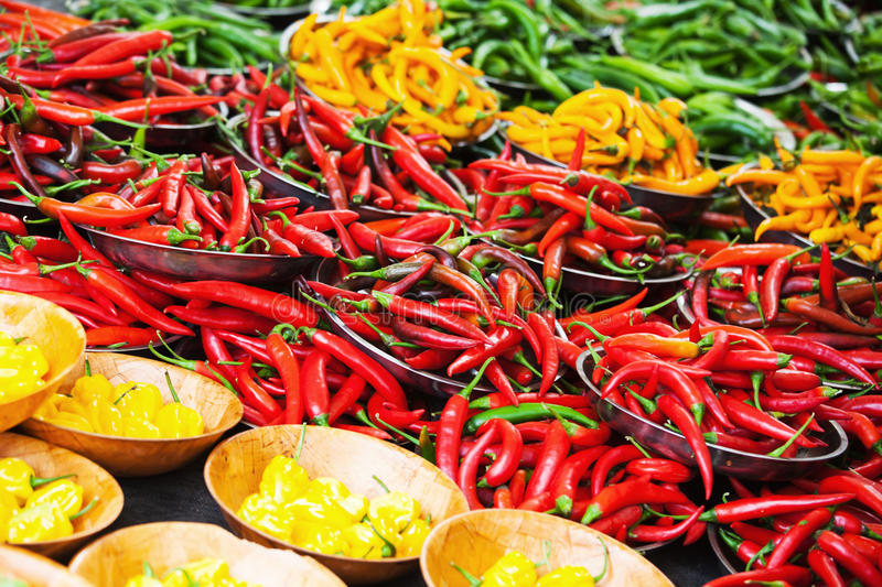 Different colored chili peppers on the market stock photography