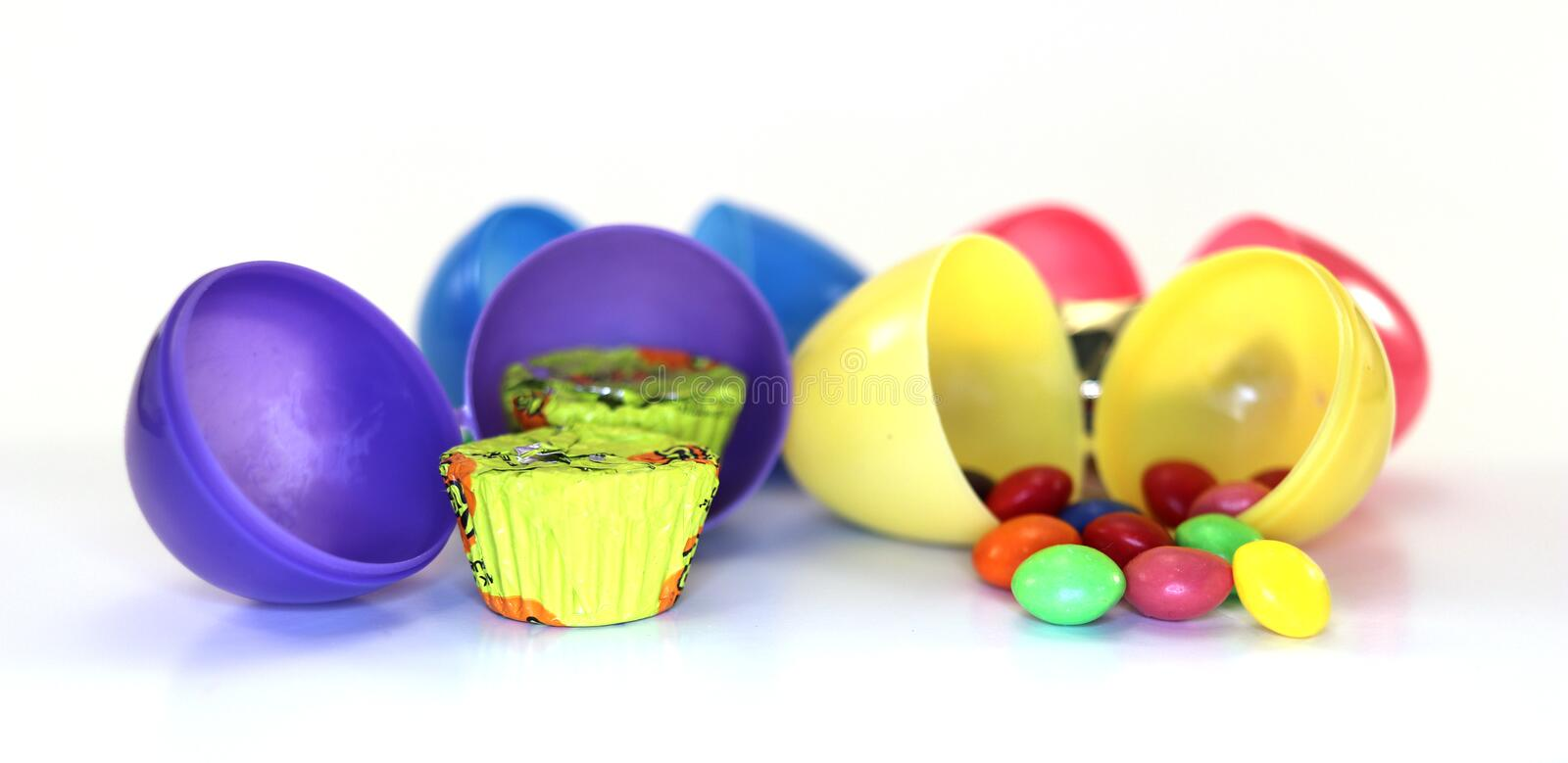 Different colored easter eggs with candy inside stock images