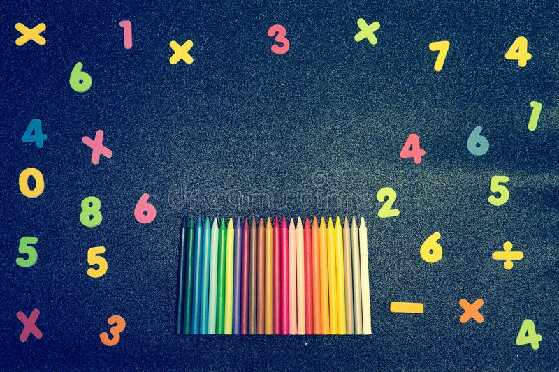 Different colored numbers and pencils on a bright background and writing space stock photo