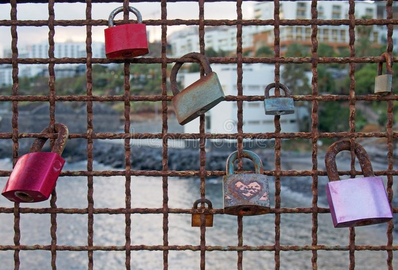 Different colored padlocks chained to a rusty fence against a seaside vacation background in evening light in funchal madeira. Old different colored padlocks stock photo