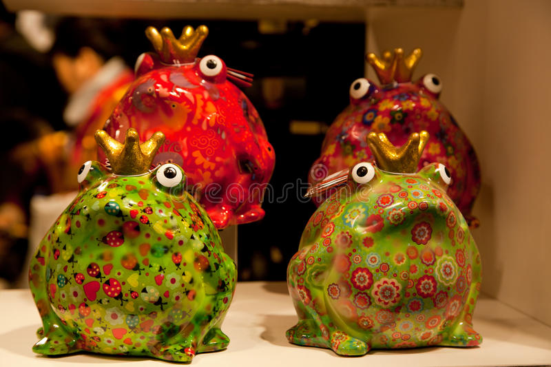 Different colored porcelain frog. Different colored decorative porcelain crowns frog sitting in funny poses stock image