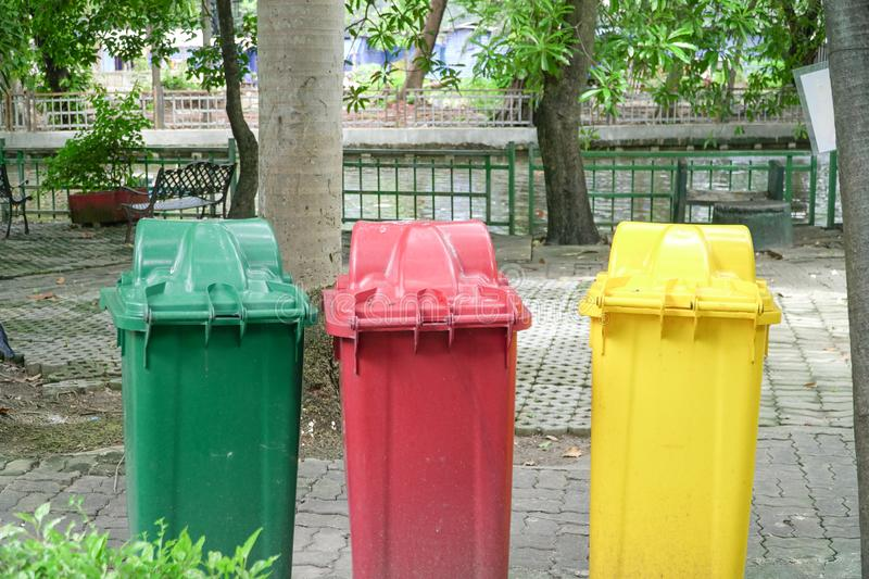 Different Colored Three Garbage Bins in public place stock photos