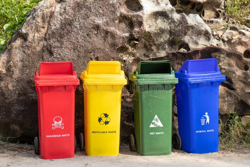 Different colored trash containers for garbage separation with sign and icon near the beach for tourist.  stock image