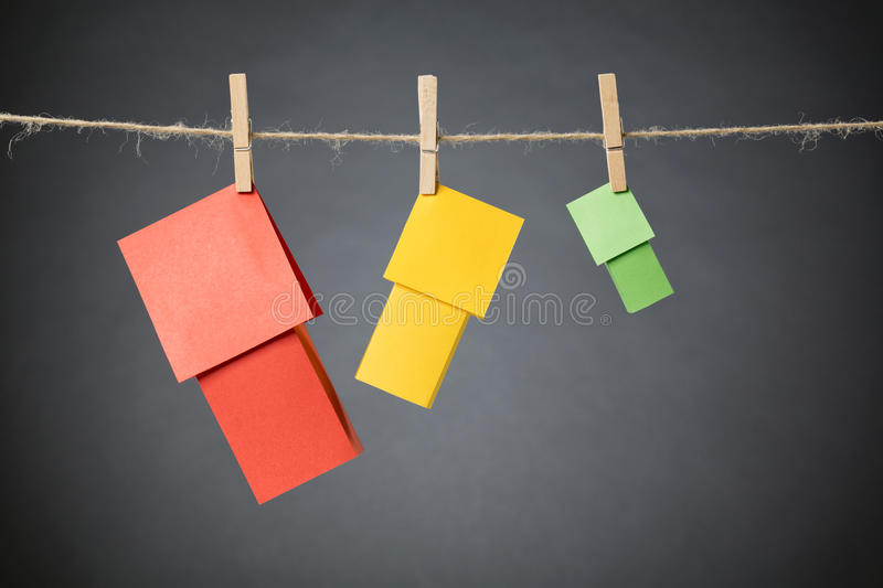 Different Colorful Houses on a Line. Three paper houses in different colors hanging on a rope line with clothespins stock images