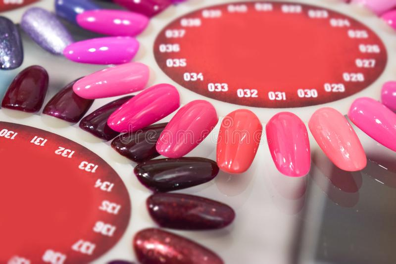 Different colorful nails polish manicure palette Background. Samples of nail varnishes. False Display Nail Art Fan Wheel Polish Pr. Actice board. Slider designs stock photos