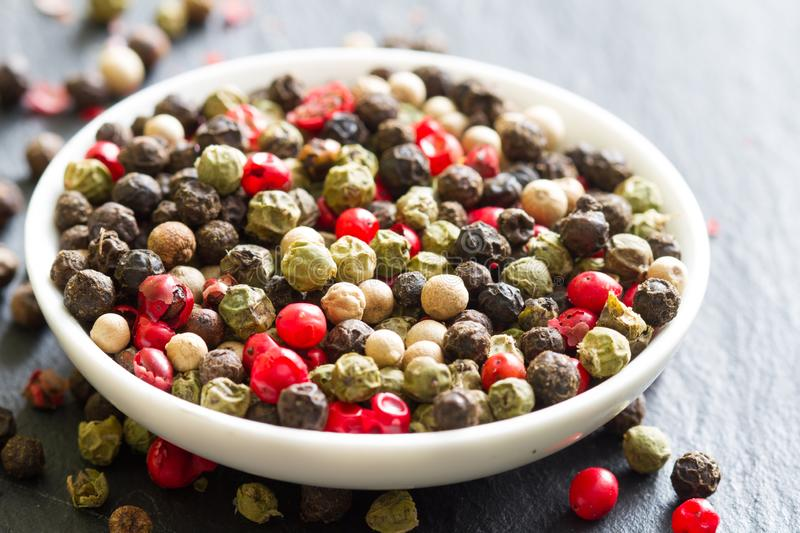 Different colorful spice white black green red pepper closeup background. Abstract royalty free stock photography