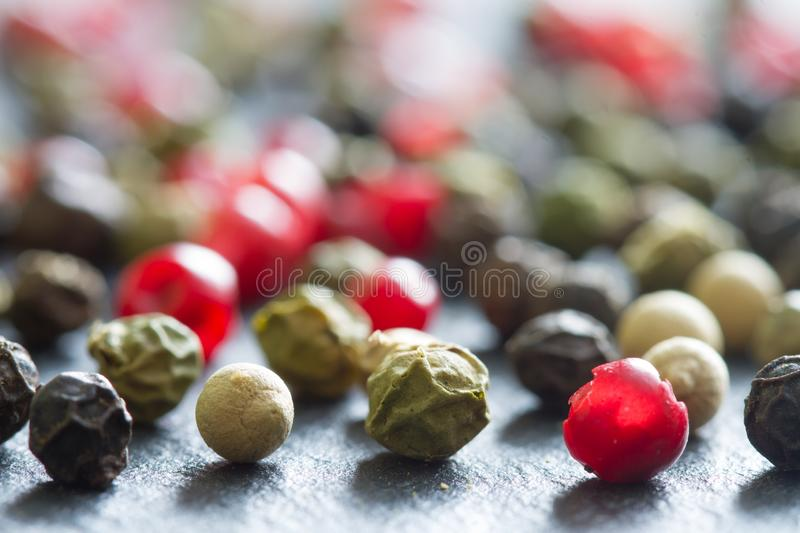 Different colorful spice white black green red pepper closeup background. Abstract stock photo