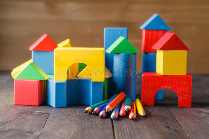 Different colors of pencils ontable with building blocks stock photography