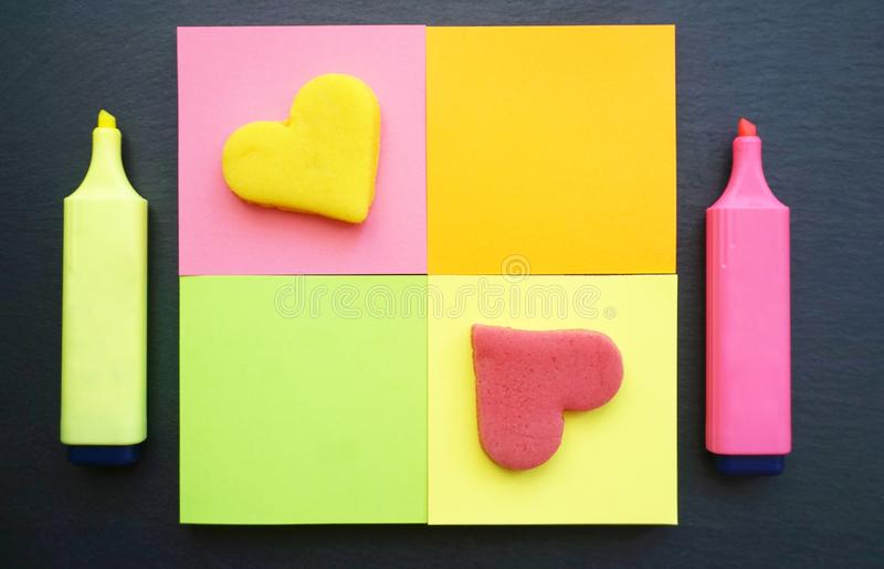 Different colors sticky note in square shaped with marker pens by side on the black board background stock photography