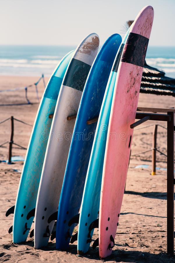Different colors of surf on a the sandy beach in Casablanca - Morocco. Beautiful view on sandy beach and ocean. Surf boards for re. Nting. Surfer school royalty free stock image
