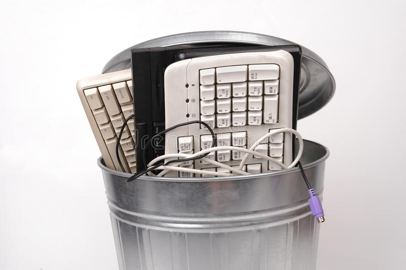 Different computer parts in trash can royalty free stock photo