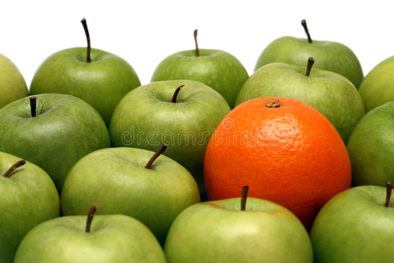 Different concepts - orange between apples. Different concepts - orange between green apples royalty free stock images