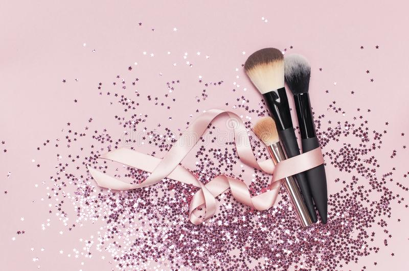 Different Cosmetic makeup brushes with pink ribbon and holographic glitter confetti in the form of stars on pink background Flat stock images