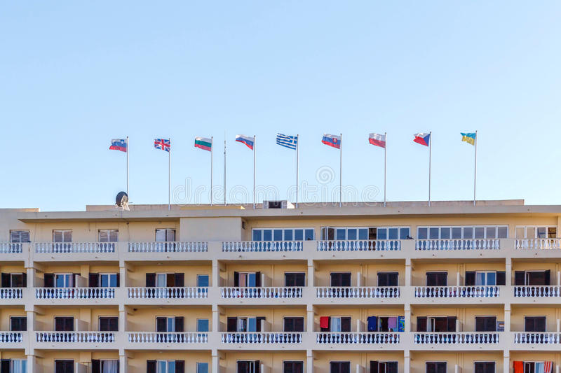 Different countries flags on hotel building royalty free stock photography