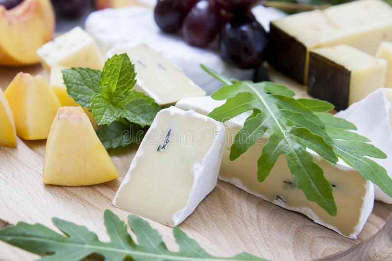 Different delicious cheeses and fruits on wooden round board royalty free stock photos