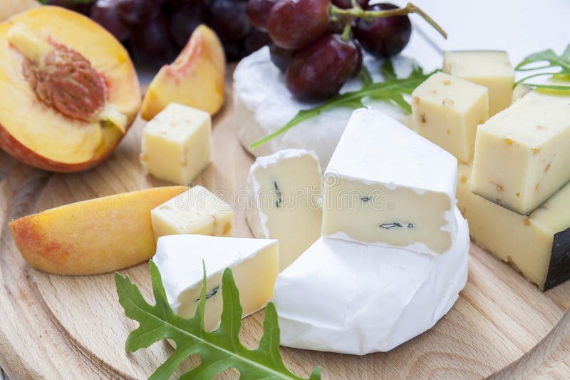 Different delicious cheeses and fruits on wooden round board stock photography