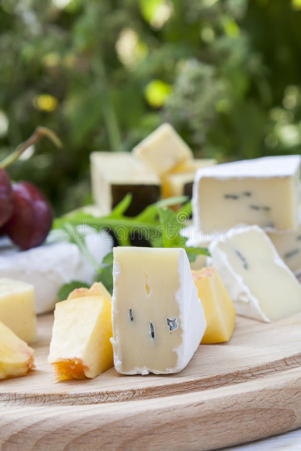 Different delicious cheeses and fruits on wooden round board royalty free stock photography