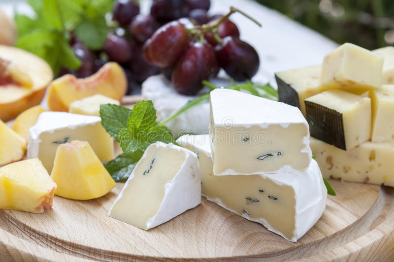 Different delicious cheeses and fruits on wooden round board royalty free stock image