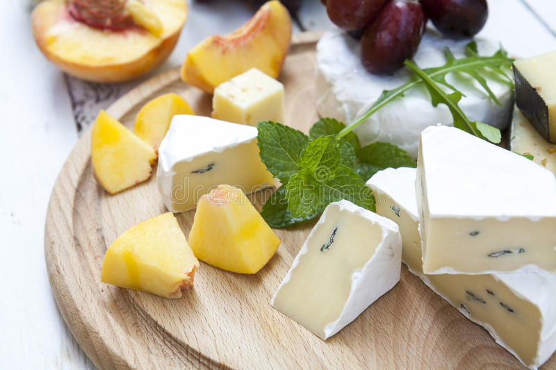 Different delicious cheeses and fruits on wooden round board royalty free stock photo