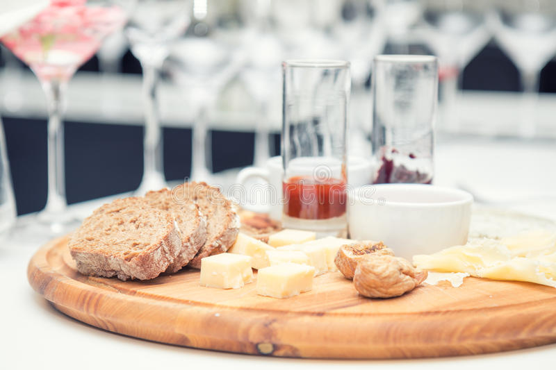 Different delicious cheeses on wooden round board stock image