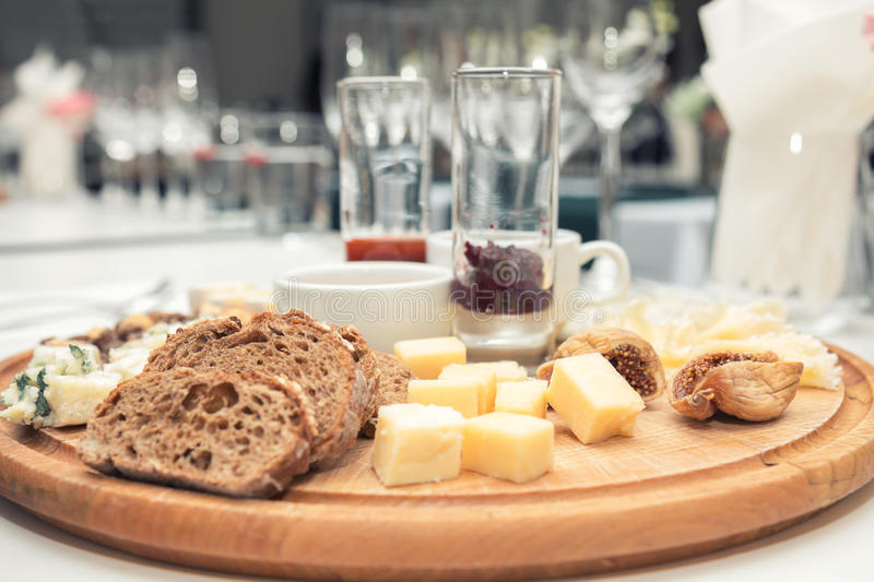Different delicious cheeses on wooden round board stock images