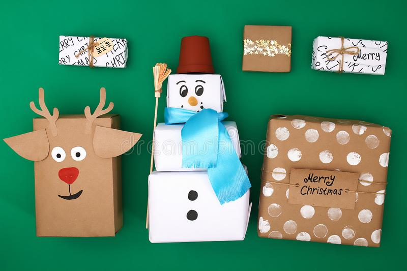 Different design of Christmas gifts from craft paper on a green background. Snowman, deer, stars, snow, handmade text. Handmade,. DIY stock photography
