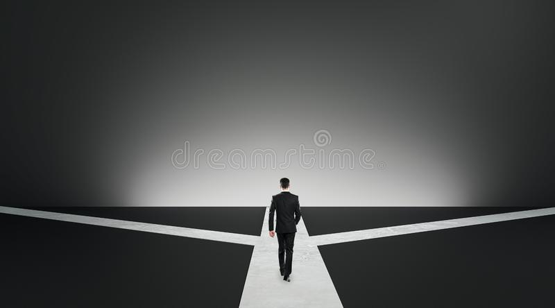 Different direction and choice concept. Back view of businessman choosing path on grey background. Different direction and choice concept stock photography
