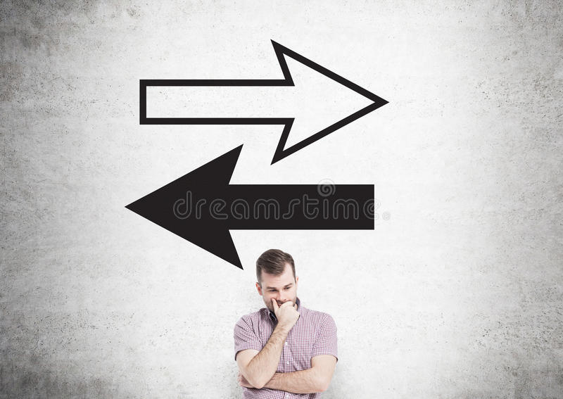 Different direction concept. With two arrow drawing and thoughtful european man on concrete wall background royalty free stock photos