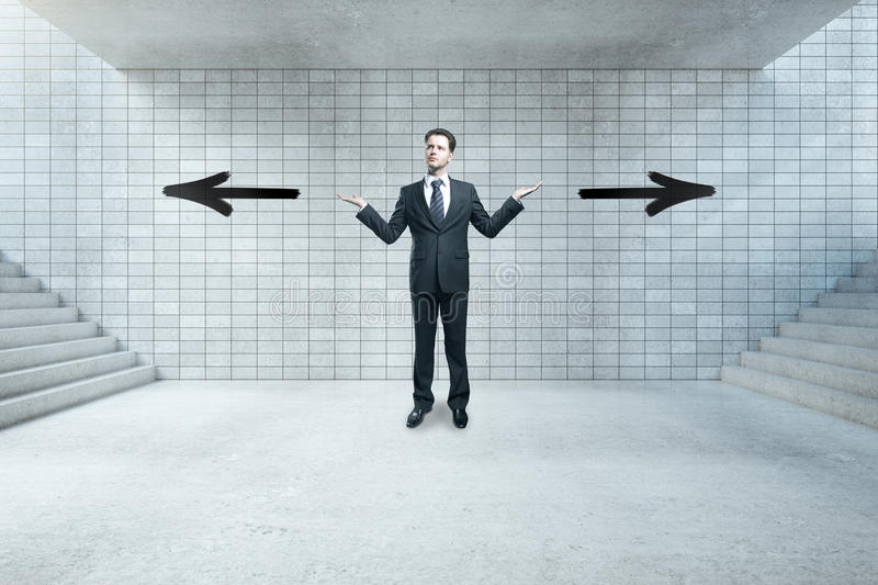 Different direction concept. Young businessman not sure where to go stock image
