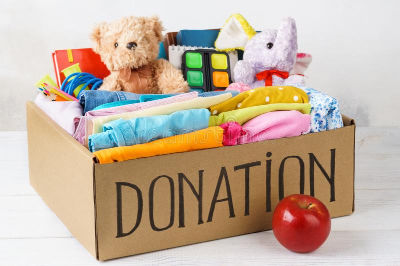 Different donations in a box - clothes, stationery and toys royalty free stock photo