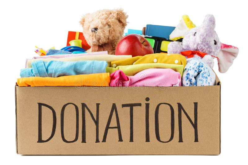 Different donations in a box - clothes, stationery and toys stock photography