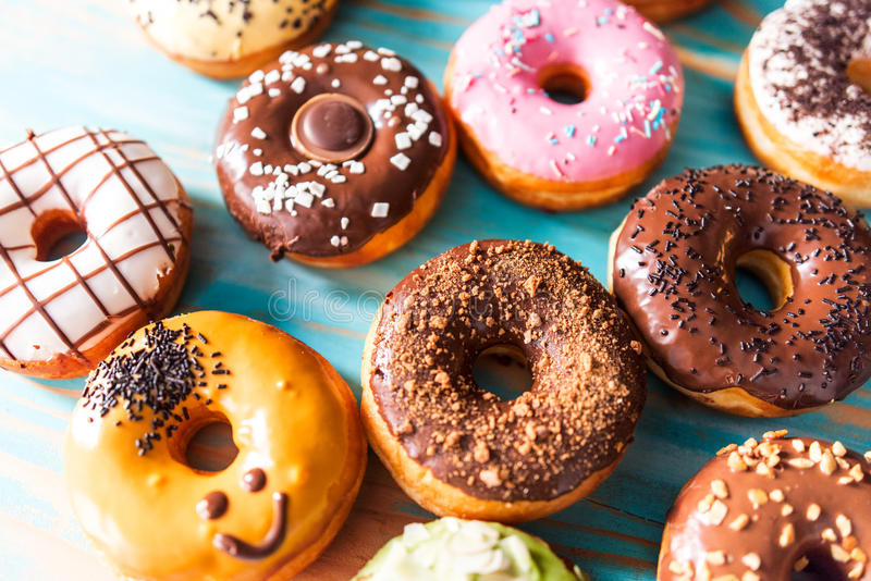 Different doughnuts. A lot of different colorful donuts. Chocolate, vanilla, caramel glazing and sprinkles, nuts and chocolate topping stock image