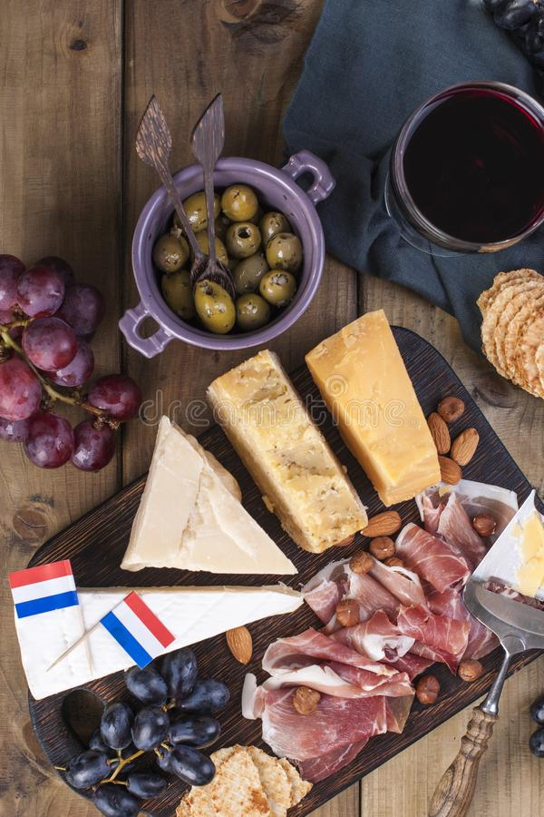 Different Dutch cheese. Ham, grapes, olives and snacks. Free space for text. Food and a glass of red wine. flat lay. copy spce stock photo