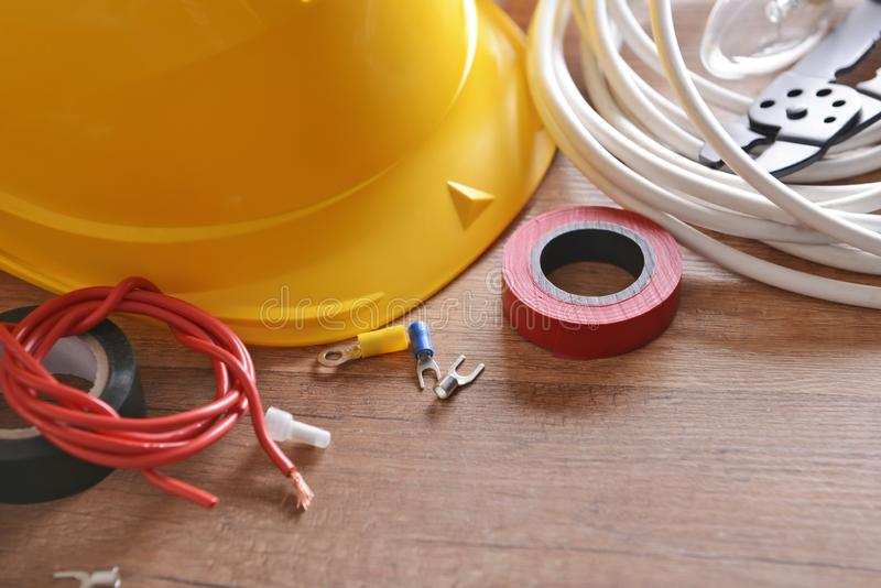 Different electrician's supplies with hard hat on table royalty free stock photos