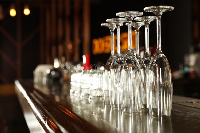 Different empty clean glasses on counter in bar. Space for text royalty free stock photography